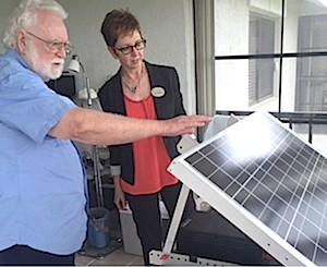 A Regency Oaks Clearwater resident shows Brookdale Director of Sustainability Marla Thalheimer the mobile, solar-powered unit he constructed as a backup power source for his apartment.