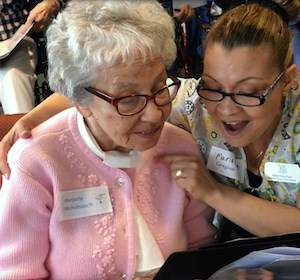 Summer House resident and Joyful Hearts choir member Marjorie Nicholson practices with Villa Gardens caregiver Maria Para.