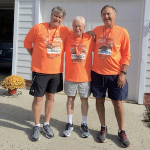 Oak Crest resident Bob Gralley, 91, is flanked by his sons, Kevin, left, and Craig after running 13.1 miles Oct. 21 in the Baltimore Running Festival.