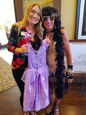 Brittany Sanfilippo, Crestavilla's director of sales and marketing, left, and Laurie Moore, manager with Gentle Transitions (a company that specializes in senior relocation) display some costumes.