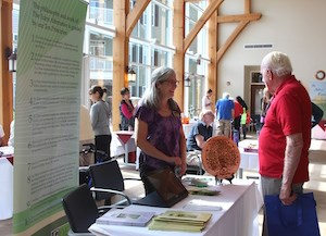 A fair attendee talks with a representative from the Eden Alternative at St. John's holistic fair.