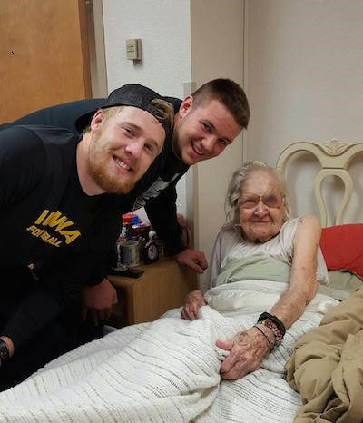 101-year-old Alice Isenhower beams with C. J. Beathard, left, and Ike Boettger of the Hawkeyes.