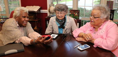 Romaine Redd, left, shares photos of a recent outing with Mary Ann Zawada and Janet Whitaker.