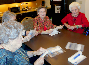 Residents of Brightwater Senior Living label bags for the Food Bank of the Golden Crescent.