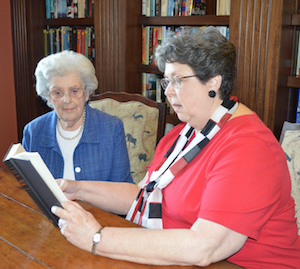 Parkway Place resident Barbara McNeir, right, reads aloud to fellow resident Betty Bryant.