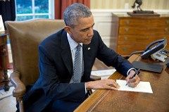 President Barack Obama signs a letter in the Oval Office on March 14. (Pete Souza)