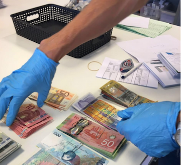 Investigators from the Netherlands count money seized during a search.