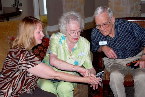 Debra Klinger, left, director of residential services at Christus St. Joseph Village, teaches residents Kay and Ray Denkhoff how to catch a Pokemon.