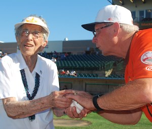 Helen Stemple strategizes with Bud Harrelson before she throws the ceremonial pitch to him.