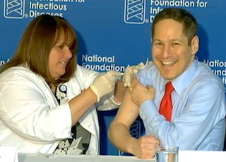 CDC Director Tom Frieden, M.D., M.P.H., right, gets a flu shot from Sharon of MedStar Visiting Nurse Association during a Sept. 29 press conference. (Photo by Lois A. Bowers)