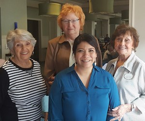 Scholarship recipient Astrid Barrios stands in front of (from left) scholarship committee members Pat Shotland, Sally Rausch (chairwoman) and Dotty Houge.
