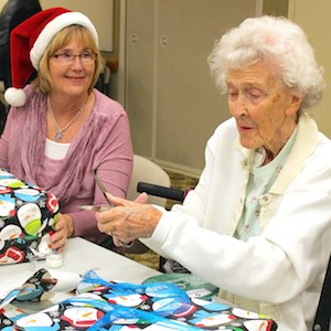 "Pat Williams, Angel Tree program coordinator for Crittenton Services, left, and Morningside resident Eunice Tuthill wrap gifts for Crittenton kids at the retirement community's recent ""wrap party."""