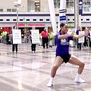 Dancers entertain airport visitors and workers while others hold signs with Alzheimer's facts as part of a flash mob arranged by American Senior Communities. (Screen grab from ASC video)