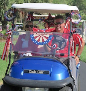 Vi at Bentley Village Executive Director Penny Smith and Head Golf Pro Stan Geer lead a procession of golf carts and bicycles in a July 4 parade.