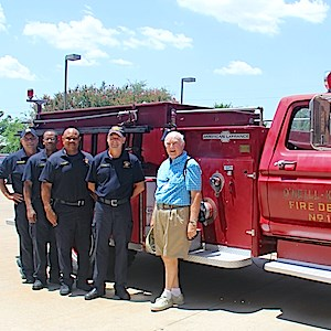 Jim O'Neill, a resident of Highland Springs retirement community, stands in front of his antique fire engine with firefighters from Dallas Station #13.