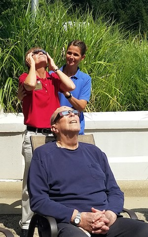 Don VanDyne, a resident of Spring Hills Middletown Assisted Living in Franklin, OH, enjoys the partial eclipse. Staff members Karen Bryant and Robin Wolfe are in the background.