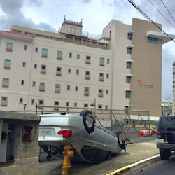 An overturned car rests on its roof outside Miramar Living after Hurricane Maria.