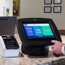 The Accushield system uses a touchscreen, badge-printing tablet to register visitors.
